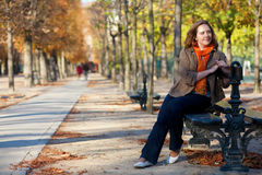 Beautiful girl at the bench by fall Royalty Free Stock Image