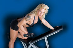 Beautiful girl on the bench in fitness center Royalty Free Stock Image