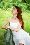 The beautiful girl on a bench in a garden Stock Photos