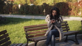 Beautiful girl on a bench in your phone looking photos. Cool autumn park. stock video