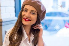 Beautiful girl in a beret sits in a cafe and smiles royalty free stock photo