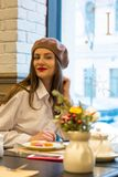 Beautiful girl in a beret sits at a table in a cafe with a cup and cake and smiles stock image