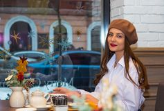 Beautiful girl in a beret sits at a table in a cafe with a cup of tea royalty free stock photo
