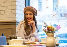 Beautiful girl in a beret sits at a table in a cafe with a cup of tea and macaroons royalty free stock images