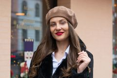 Beautiful girl in a beret stands near the window cafe royalty free stock images