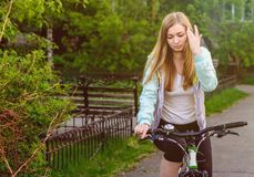 A beautiful girl on a bicycle adjusts her hair stock image