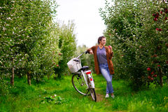 Beautiful girl with a bicycle in an apple orchard Royalty Free Stock Photo