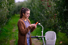 Beautiful girl with a bicycle in an apple orchard Royalty Free Stock Images