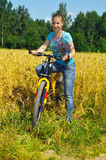 Beautiful girl on bicycle near the field Stock Image