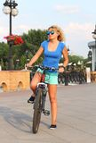Beautiful girl in a bicycle in the town stock photography