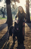 Beautiful girl with big black dog stock photos
