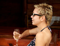 Beautiful girl in bikini drinking champagne at the bar Royalty Free Stock Photos