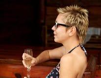 Beautiful girl in bikini drinking champagne at the bar Royalty Free Stock Photos