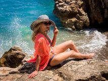 Beautiful girl in a bikini, hat and tunic sunbathing Royalty Free Stock Images