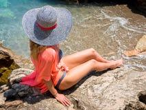 Beautiful girl in a bikini, hat and tunic sunbathing Stock Photos