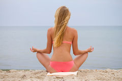 Beautiful girl in bikini sitting and looking at the sea. Yoga and meeting the dawn. Stock Images
