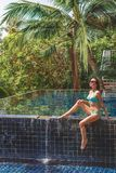 Beautiful girl in bikini sitting on poolside. And looking up stock photo