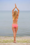 Beautiful girl in bikini standing and looking at the sea. Yoga and meeting the dawn. Tranquility and meditation Royalty Free Stock Images