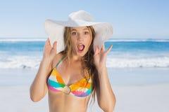 Beautiful girl in bikini and straw hat looking at camera on beach Stock Image