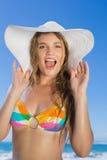 Beautiful girl in bikini and straw hat looking at camera on beach Stock Photography