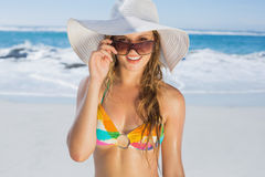Beautiful girl in bikini and straw hat smiling at camera on beach Royalty Free Stock Photography