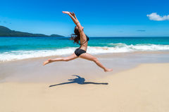 Beautiful girl in bikinis jumping on tropical beach Stock Image