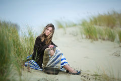 Beautiful girl with a birdcage in a dune Royalty Free Stock Image