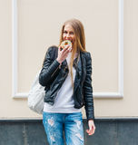 Beautiful girl bites a delicious donut walking on the streets of European city. Warm spring. Outdoor Stock Photos