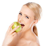 Beautiful girl is biting fresh apple Royalty Free Stock Images
