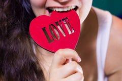 Beautiful girl biting red heart Stock Photography