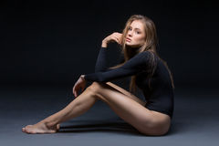 Beautiful girl in black body. Beautiful young woman in black body wear sitting on floor. Over black background. Copy space Royalty Free Stock Image