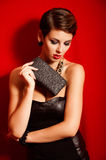 Beautiful girl with a black clutch bag in her hand Royalty Free Stock Photo