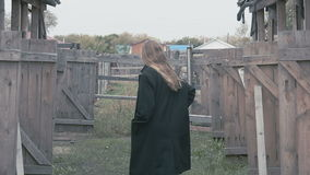Beautiful girl in a black coat against the background of the village fence stock video footage