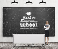 A beautiful girl with black document folder and teacher's desk in a modern school. A black chalkboard on the wall with written dow Stock Photo