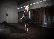 Beautiful girl in black dress dancing at night on summer terrace Royalty Free Stock Photos