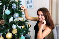 Beautiful girl in a black dress decorates Christmas tree Stock Photography
