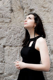 Beautiful girl with black dress and earrings looking up, cement wall Royalty Free Stock Images