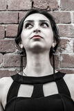 Beautiful girl with black dress and earrings looking up, wall made of bricks.  Stock Image
