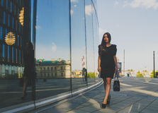 Beautiful girl in a black dress goes in the background of the business center Royalty Free Stock Photo