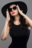 Beautiful girl in black dress, hat and sunglasses. Studio portrait of beautiful girl in black dress, hat and sunglasses on gray background Royalty Free Stock Image