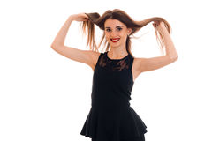 Beautiful girl in black dress holding the hands of her hair and smiling Royalty Free Stock Photos