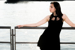 Beautiful girl with black dress leaning back enjoying the sun Royalty Free Stock Photos