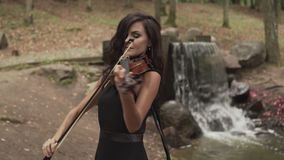 Beautiful girl in black dress playing violin in forest with waterfall. At background. Young violinist plays with inspiration stock video