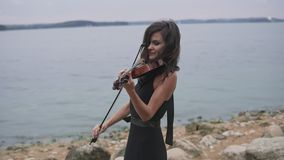 Beautiful girl in black dress plays violin at sea background. Art concept in 4k stock video