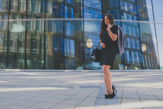 Beautiful girl in black dress with purse and jacket in hand on the background of the business center Royalty Free Stock Photo