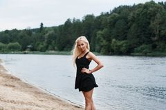 Beautiful girl in black dress on the river bank. Beautiful girl in black dress on the river Stock Image