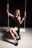 Beautiful girl in black dress swinging Stock Photography