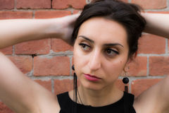 Beautiful girl with black earrings holding her hair up. Wall made of bricks Royalty Free Stock Photos