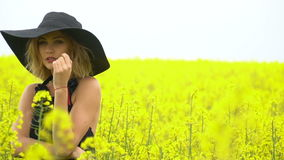 Beautiful girl in black among the field of field of canola stock video footage
