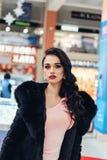 Beautiful girl in a black fur coat. Beauty Fashion Model Girl in Mink Fur Coat. Beautiful Woman in Luxury Brown Fur Jacket . Winter Fashion Royalty Free Stock Photos